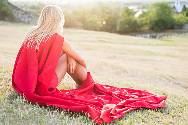 Blonde woman laying in grass outdoor stock photo