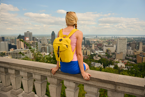 Blonde woman looking at Montreal downtown skyline cityscape.