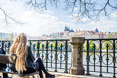 Blonde woman looking at of Vltava river during day Castle of Prague in background