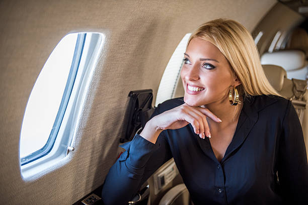 Blonde woman looking through the airplane window stock photo