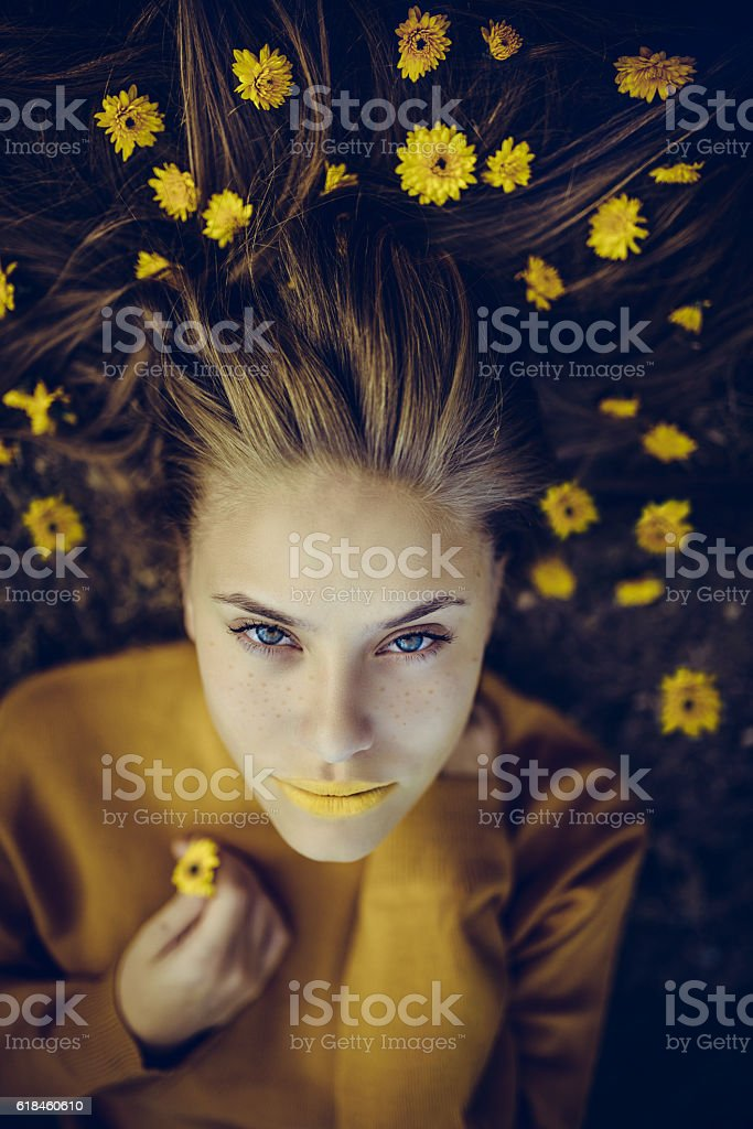 Blonde Woman Lying on Meadow with Yellow Flowers in Hair stock photo