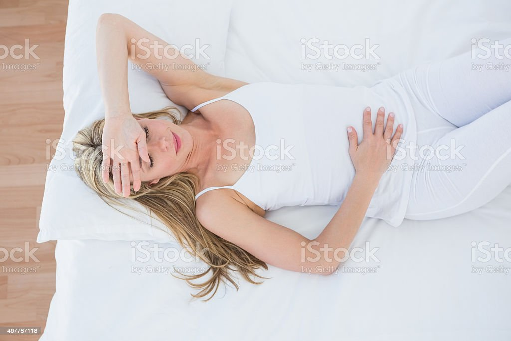 Blonde woman lying suffering from stomach pain stock photo