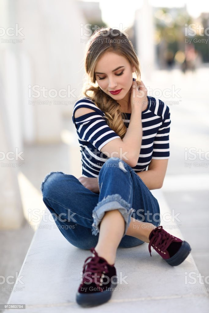 Blonde woman, model of fashion, sitting in urban background. stock photo