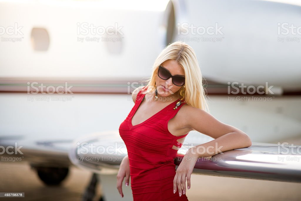 Blonde woman next to wing of jet aeroplane stock photo