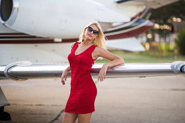 Blonde woman next to wing of jet airplane stock photo