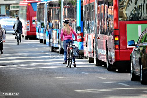 istock Blonde woman on bike and lane of buses 519041792