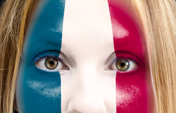 Blonde woman painted on her face the flag of France stock photo