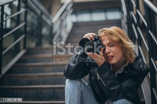 One woman, sitting outdoors on steps, holding a camera, taking pictures.