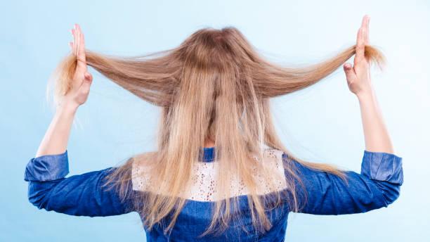 sarışın kadın saçla oynuyor. - kabarık saç stok fotoğraflar ve resimler