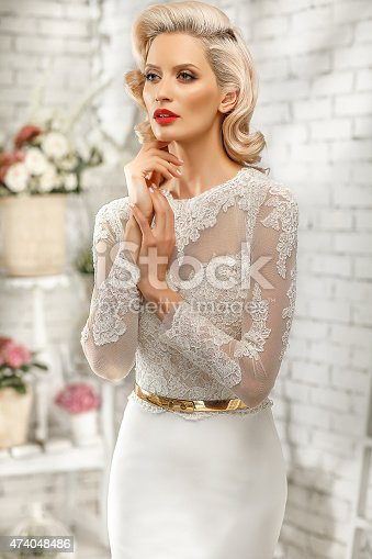Blonde Woman Posing In A Tight White Dress With A Gold