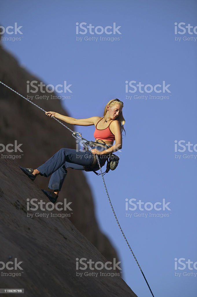 Blonde Woman Rappelling Against Blue Sky royalty-free stock photo