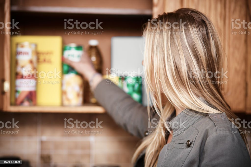 Blonde woman reaching into kitchen cupboard for canned food. stock photo