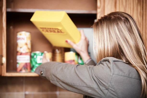 blond kvinna att nå in i köksskåp för spannmål paket - looking inside inside cabinet bildbanksfoton och bilder