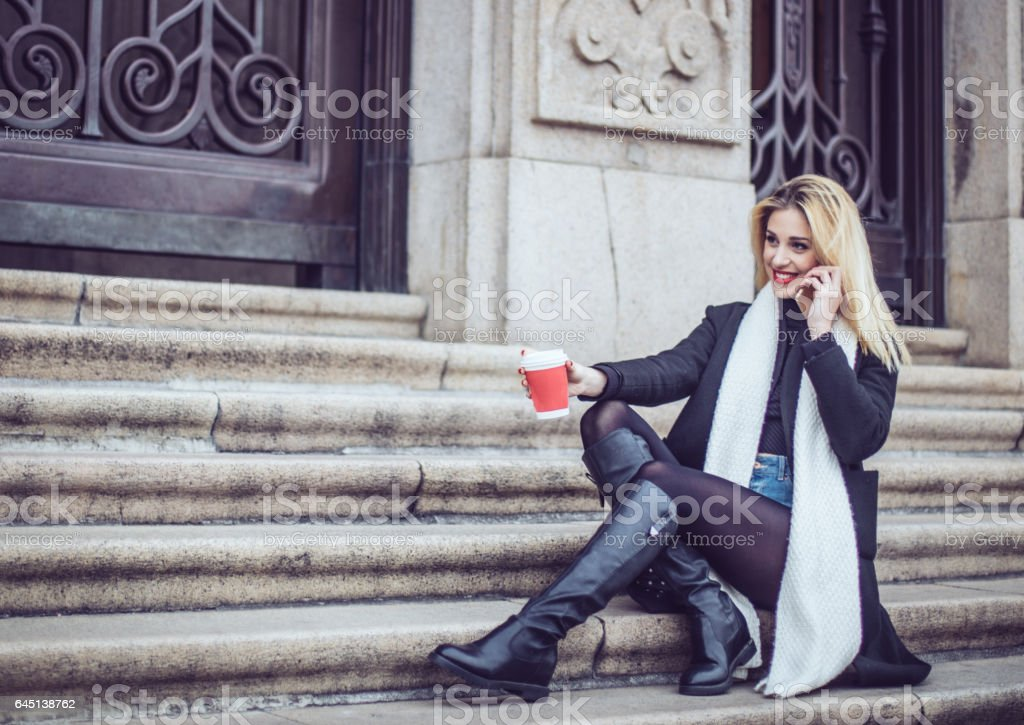 Blonde woman relaxing on steps stock photo