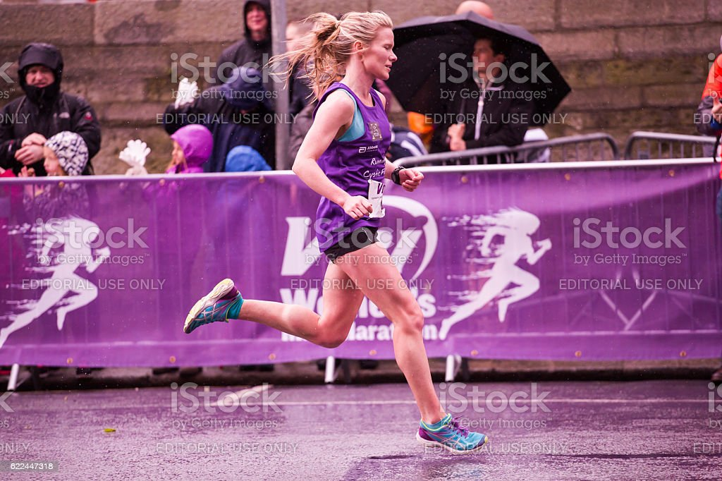 Blonde woman running the marathon stock photo