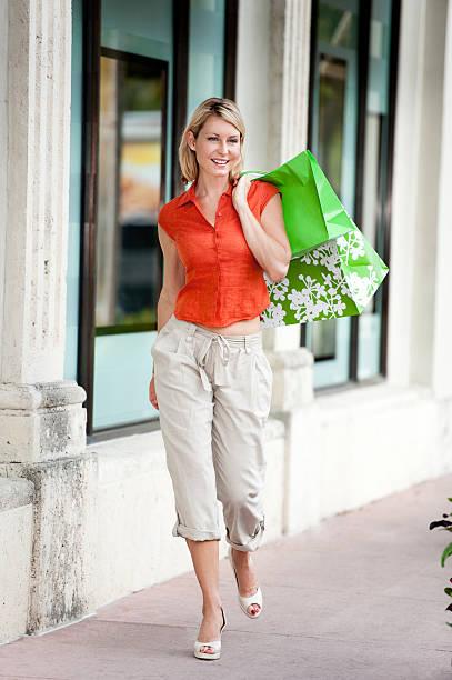 blonde frau shopping mit taschen - leinenhosen frauen stock-fotos und bilder