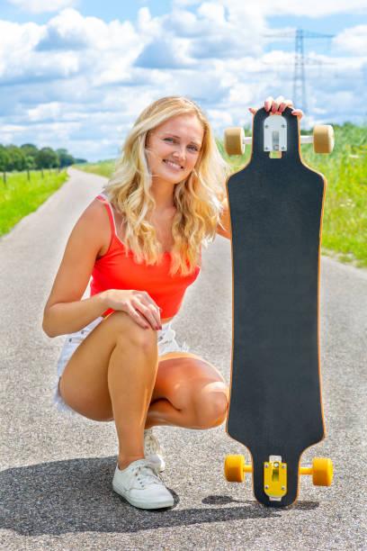 Blonde woman showing longboard on rural road stock photo