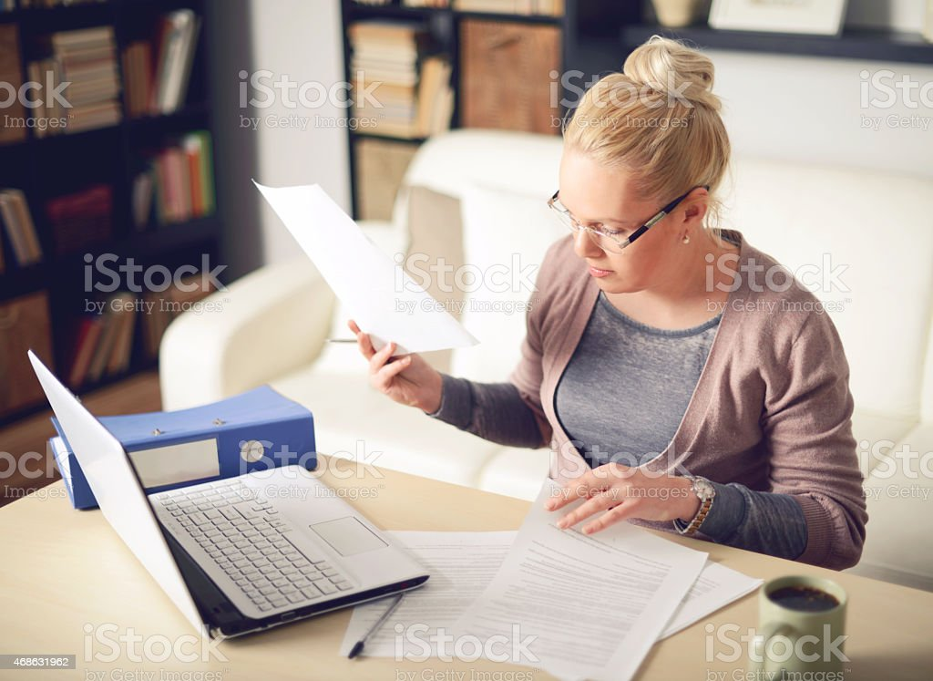 Blonde woman shuffling through papers working from home stock photo
