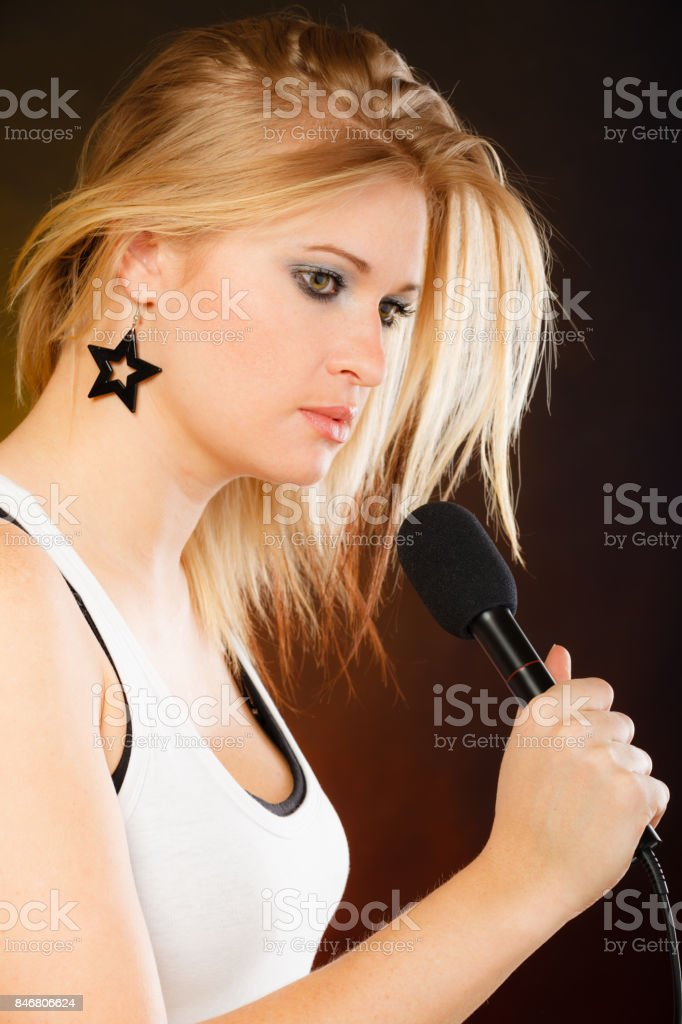 Blonde woman singing to microphone stock photo