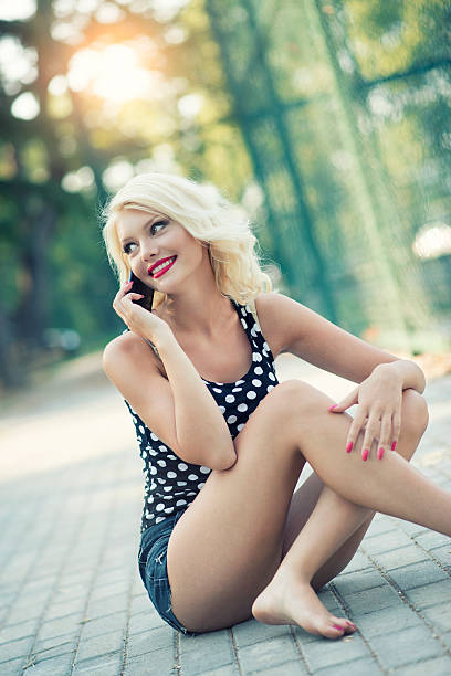 Blonde Woman Sitting and Talking on Phone in City Park stock photo