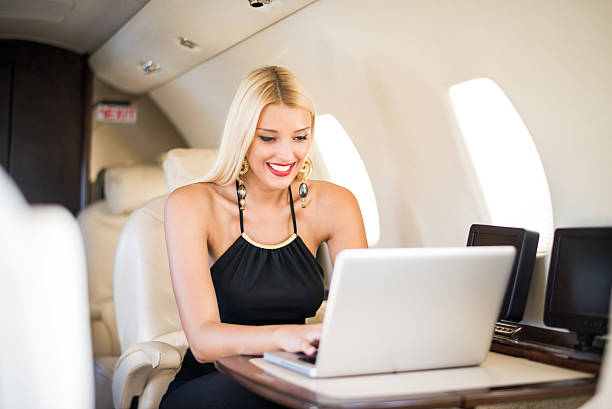 Blonde woman sitting in private jet airplane stock photo