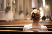 Blonde woman sitting on a church bench praying