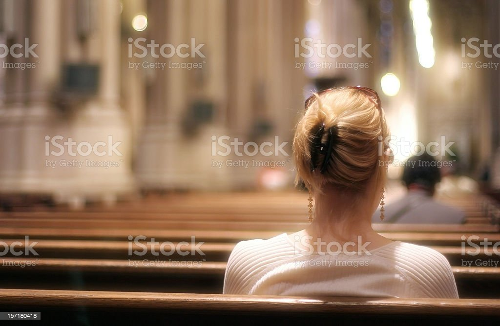 Blonde woman sitting on a church bench praying stock photo