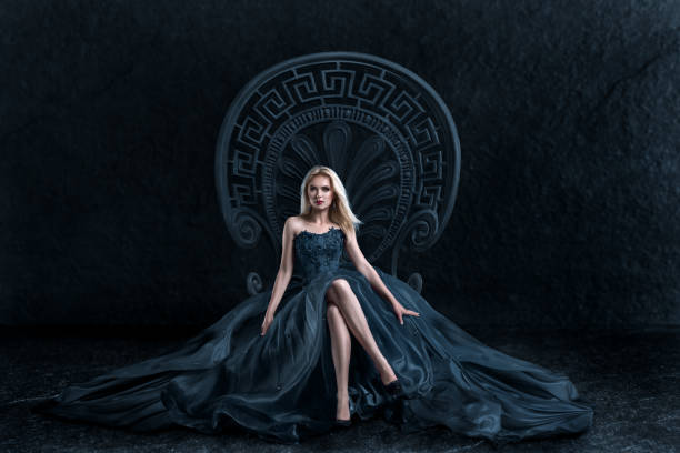 blonde woman sitting on the throne - gothic fashion stock photos and pictures