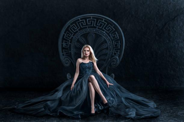 blonde frau sitzt auf dem thron - gothic kleid stock-fotos und bilder