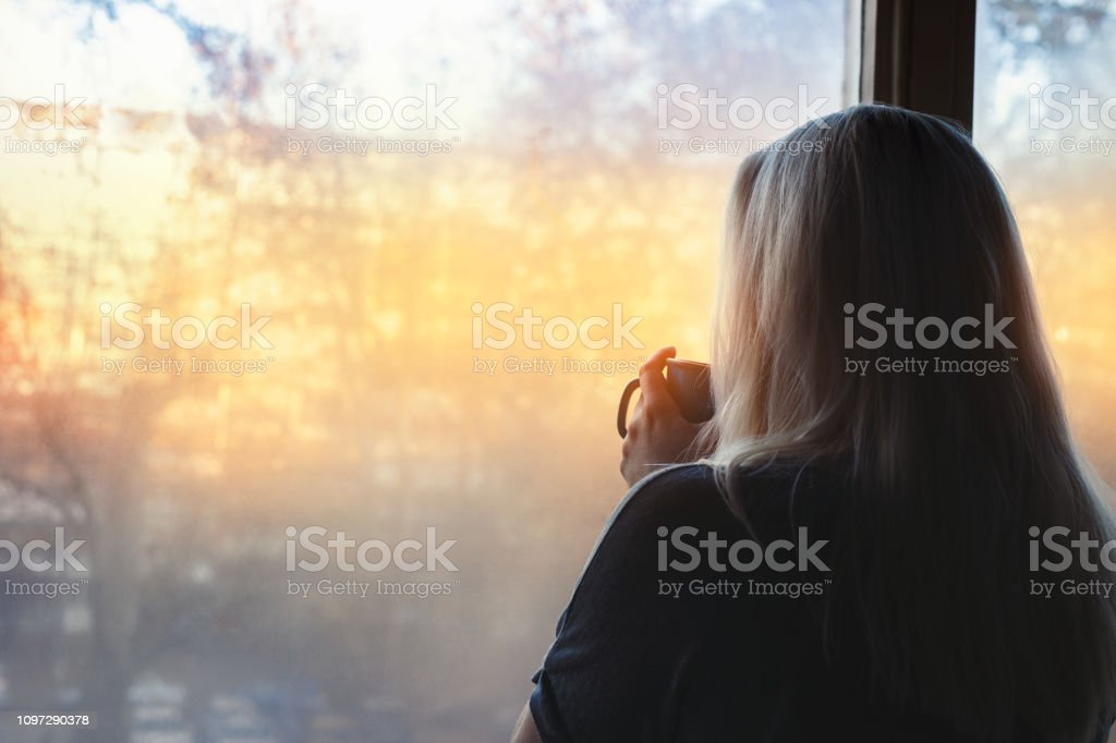 Blonde woman standing by the window, with coffee cup in hands, looking out into the morning light - Zbiór zdjęć royalty-free (Budzić się)