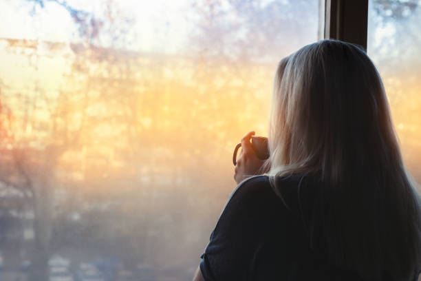 Blonde woman standing by the window, with coffee cup in hands, looking out into the morning light Blonde woman standing by the window, with coffee cup in hands, looking out into the morning light desolation stock pictures, royalty-free photos & images