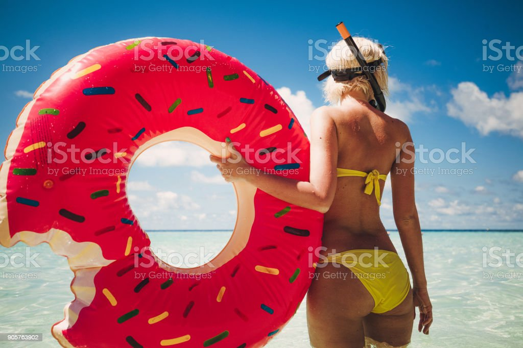 Blonde woman standing in shallow water with snorkel equipment, Maldives stock photo