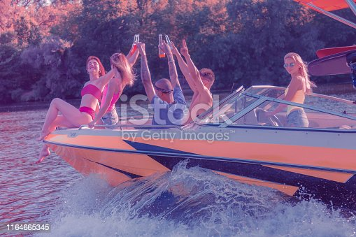 Joyful friends. Young blonde woman steering a boat while her friends drinking soft beverages on the bow