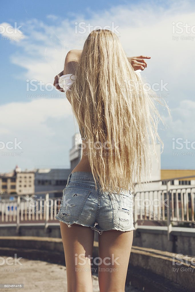Blonde woman taking off  t-shirt stock photo
