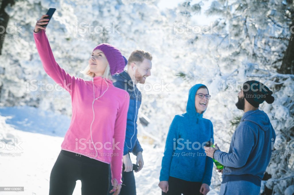 One attractive blonde sportswoman is standing and taking a selfie....
