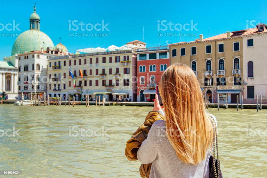 Blonde woman tourist taking photos in Venice canal, Italy royalty-free stock photo