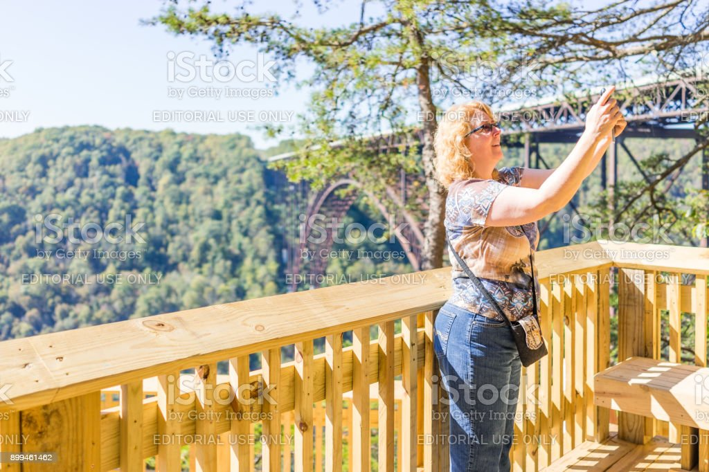 Blonde woman tourist taking selfie photo picture in front of overlook of West Virginia green mountains in spring, summer or autumn fall at New River Gorge Bridge stock photo