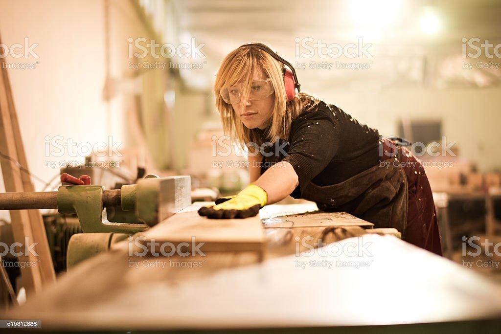 Blonde woman using plank cutter stock photo