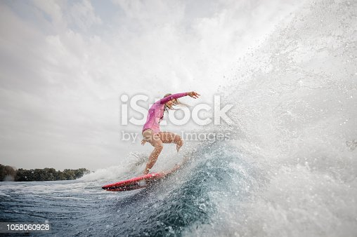 Active blonde woman wakesurfer dressed in pink swimsuit riding down the blue splashing wave against grey sky on a cloudy day