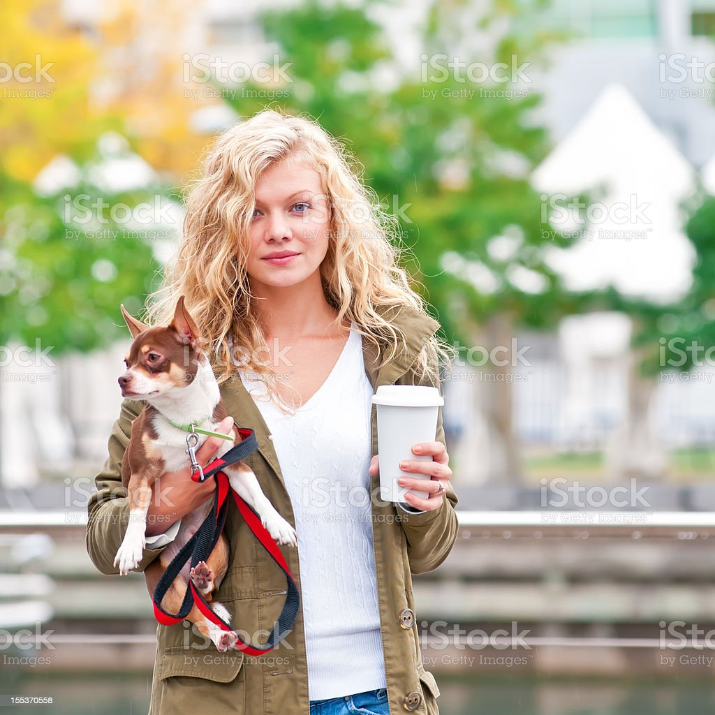 Blonde woman walking with her Chihuahua dog - IV royalty-free stock photo