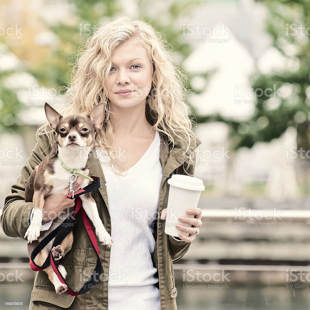 Blonde woman walking with her Chihuahua dog - IX royalty-free stock photo