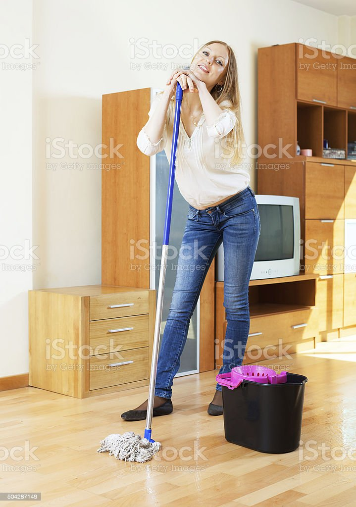 Blonde woman washing parquet stock photo