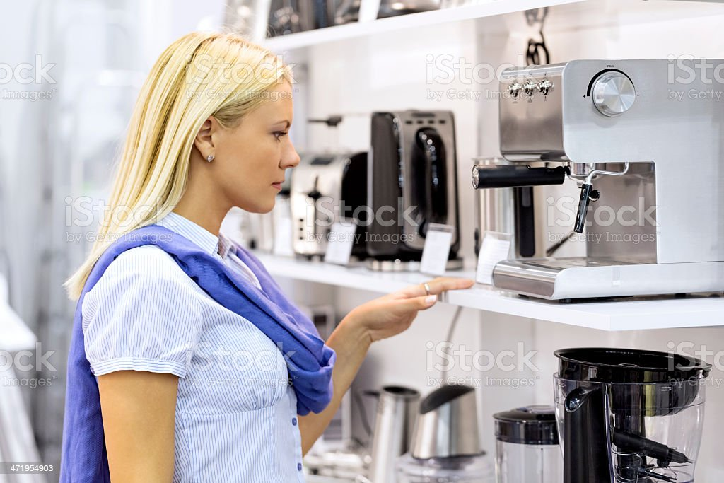 Blonde woman wearing blue shopping for an espresso machine stock photo