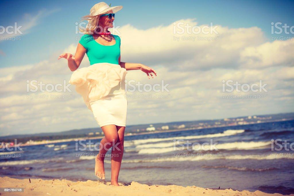 Usando vestido de mulher loira andando na praia - foto de acervo