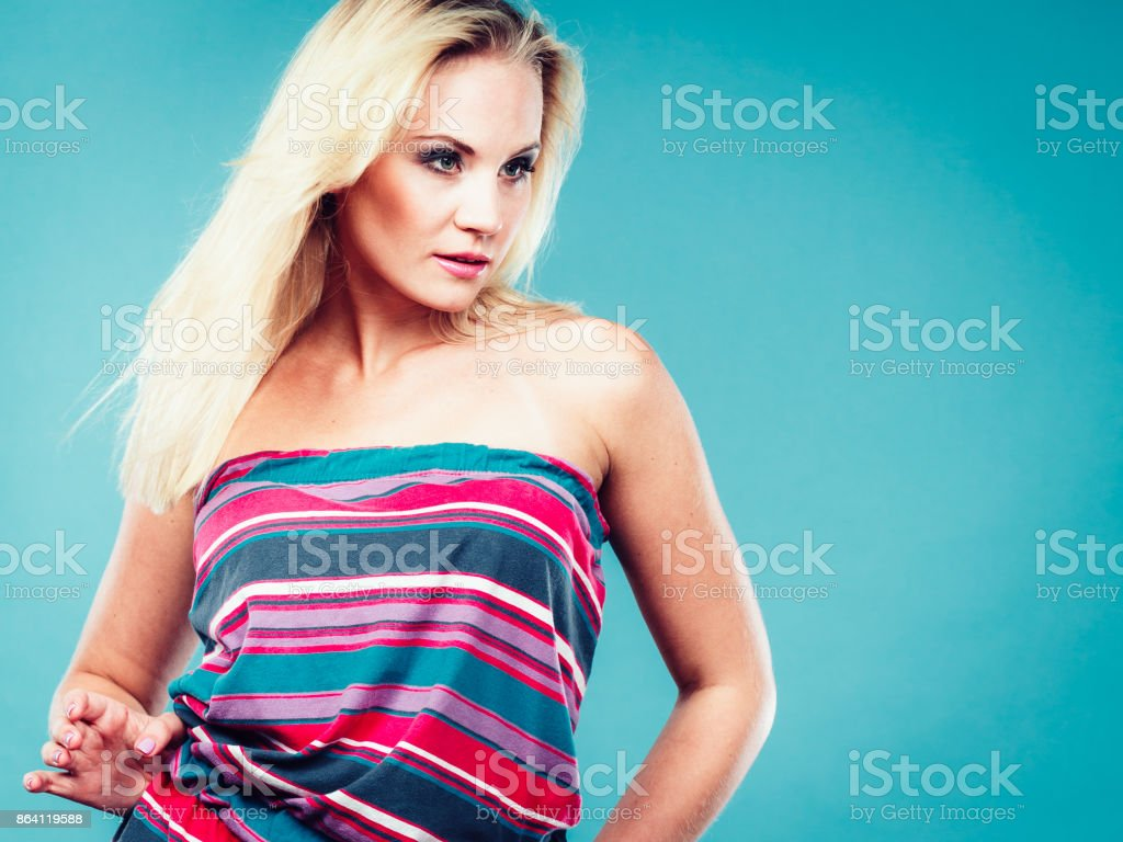 Blonde woman wearing short colorful striped dress royalty-free stock photo