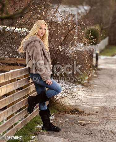 Blonde woman, winter fur coat, looking at camera