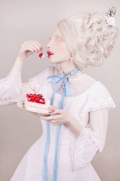 A blonde woman with a beautiful luxurious rococo style hairdo in a white dress with a blue ribbon around her neck with and cake in hand on a gray background. stock photo