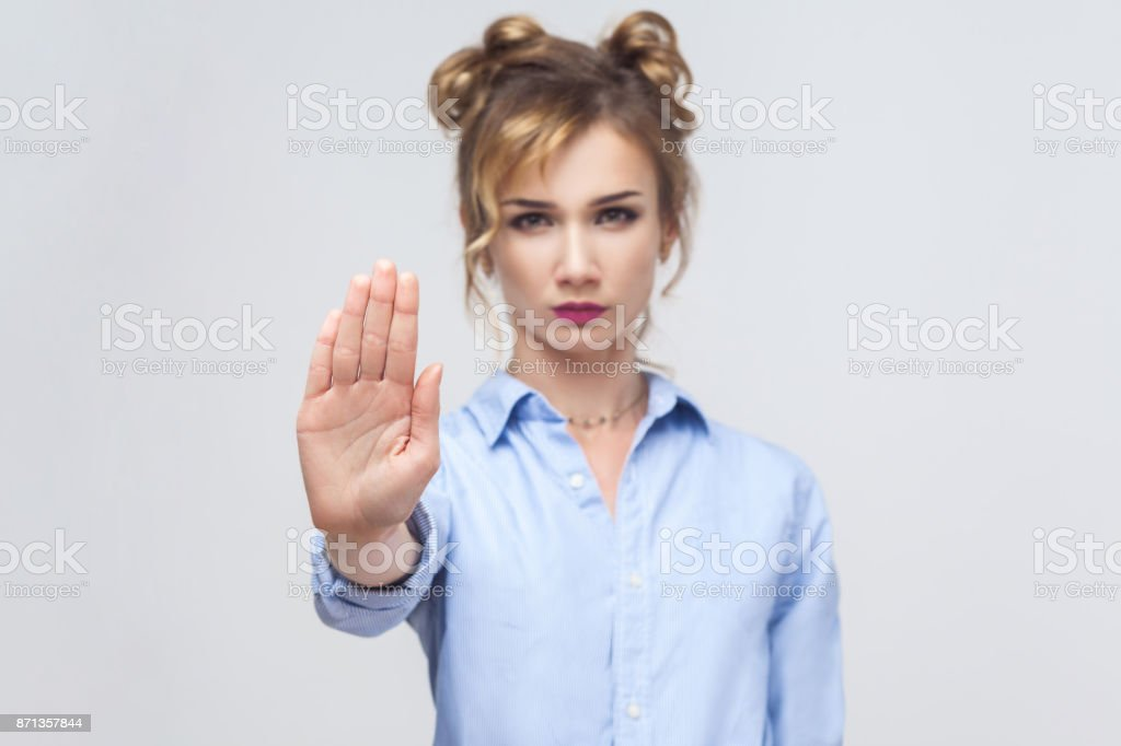 Blonde woman with bad attitude making stop gesture with her palm outward, saying no, expressing denial or restriction. stock photo