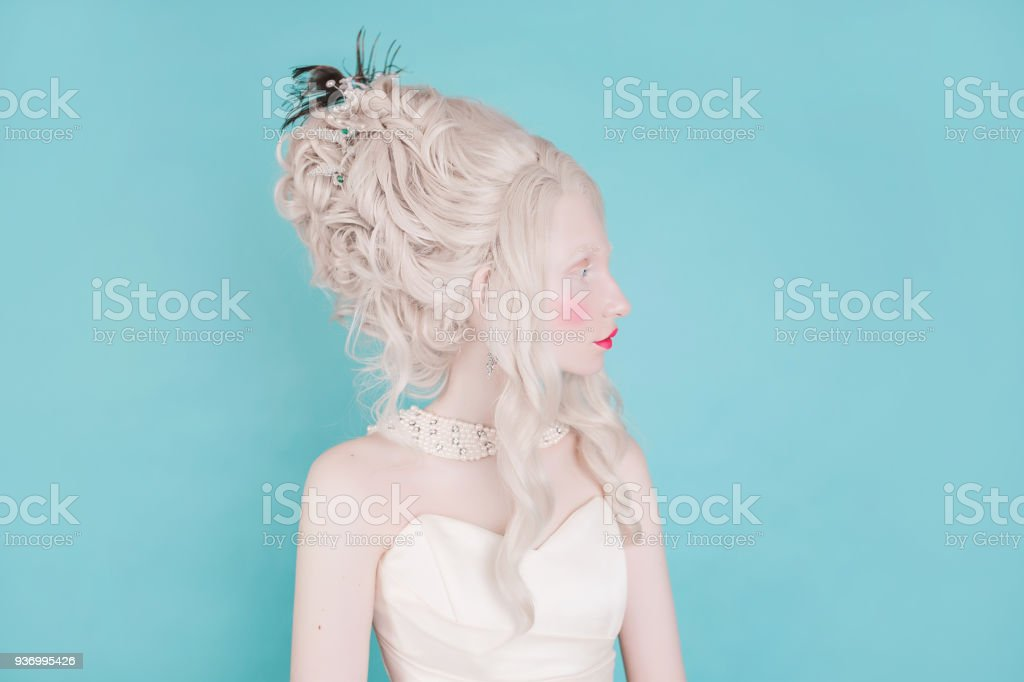 Blonde woman with beautiful luxurious rococo hair style in white dress on a blue background stock photo