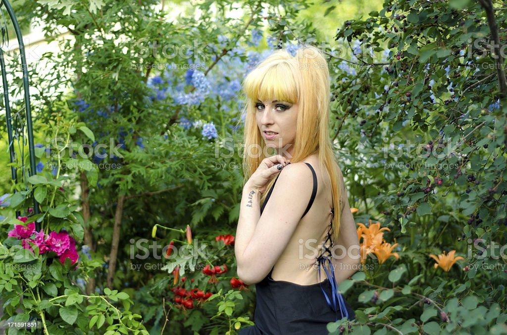 Blonde woman with corset piercing in flower garden. stock photo